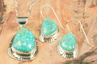 Genuine High Grade Kingman Web Turquoise set in Sterling Silver. Beautiful Pendant and Earrings Set. Created by Navajo Artist Phillip Sanchez. Signed by the artist. The Mineral Park Mine, in the Cerbat Mountains 14 miles northwest of Kingman, was first mined by Indians centuries before white man came to the area. It is one of the three sites of prehistoric mining localities in the state of Arizona. Mineral Park was the most extensively worked area by the Indians of the three. S.A. Chuck Colbaugh found a cache of stone hammers uncovered in ancient trenches and tunnels, when he had the turquoise mining concession in May of 1962. Ithaca Peak and Turquoise Mine &#40;formally called Aztec Mountain or Aztec Peak&#41; are the most famous of the peaks in the area containing turquoise.